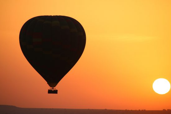 A hot air balloon in the sunset of the Serengeti
