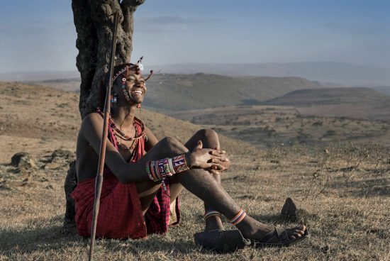 Maasai warrior laughing on a cliff top in Kenya