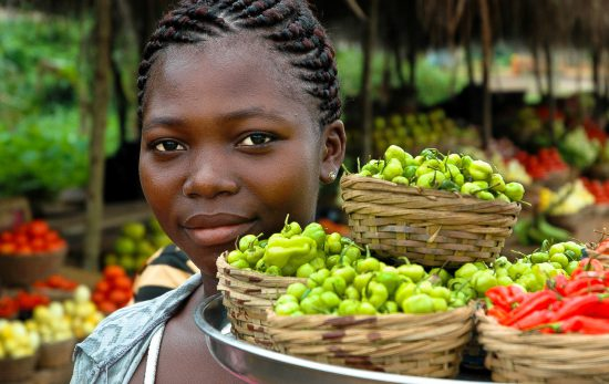 A girl with baskets of fruit at a market in Ghana