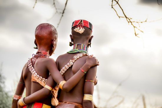 Traditionally dressed African girls walking arm in arm
