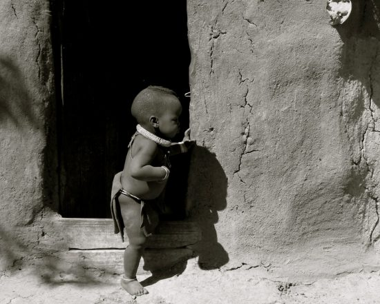 A naked child stepping out of his home in Zanzibar