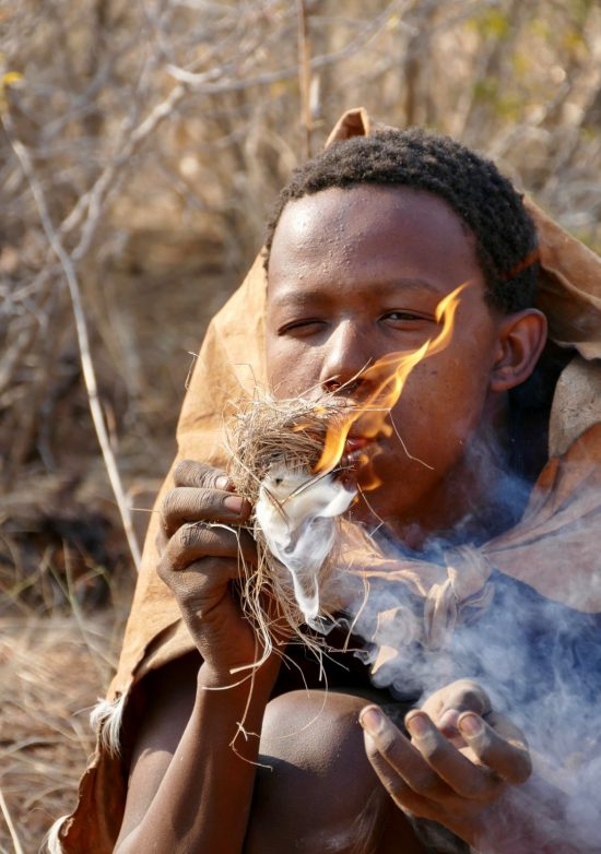 A bushman starting a fire using traditional methods