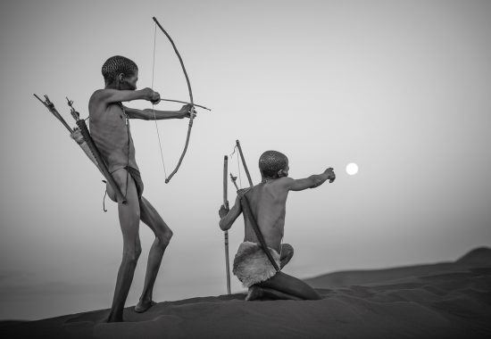 San and a full moon in the Namibian desert