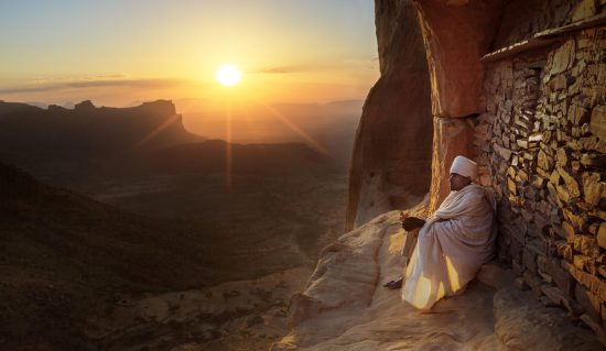 An Ethiopian orthodox priest sitting in front of one of the UNESCO World Heritage rock hewn churches in Tigray, Ethiopia
