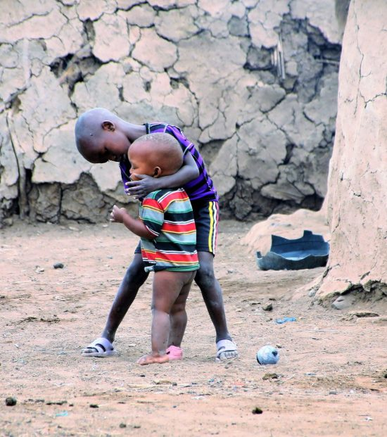 An older brother helping his younger brother in a rural African setting