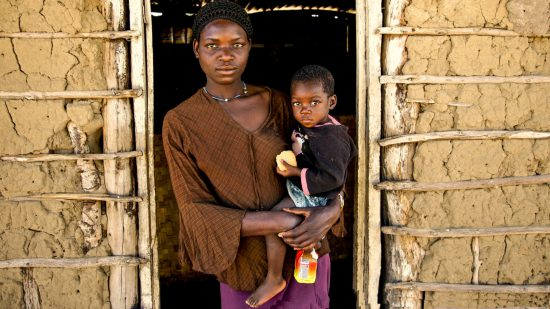 A mother and a child stand at the door of the home in Botswana