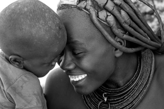 A Himba mother smiling at her baby in Namibia.