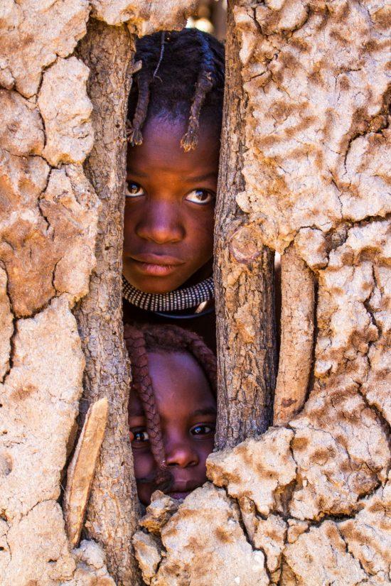 Himba girls peeking through a mud hut wall in Namibia