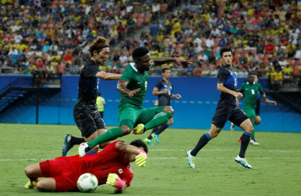 Nigeria's player Ezekiel leaps over Japan's goalkeeper Kushibiki during the Rio 2016 Olympic Games men's First Round Group B football match Nigeria vs Japan, at the Amazonia Arena in Manaus on August 4, 2016. / AFP PHOTO / RAPHAEL ALVES