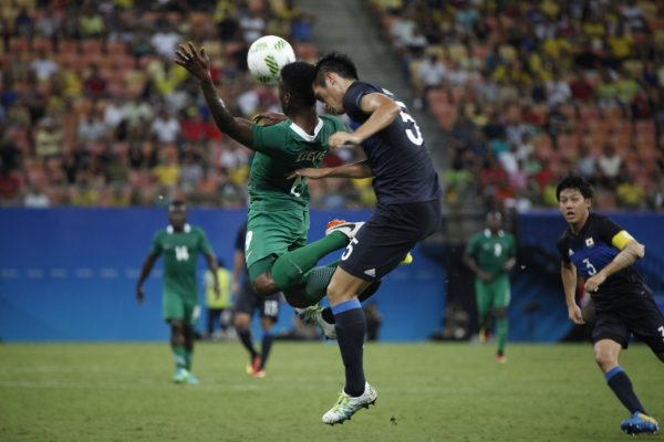 Japan's player Ueda and Nigeria's player Ezekiel fight for the ball during the Rio 2016 Olympic Games men's First Round Group B football match Nigeria vs Japan, at the Amazonia Arena in Manaus on August 4, 2016. / AFP PHOTO / RAPHAEL ALVES