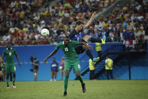 Japan's player Shiotani and Nigeria's player Sadiq fight for the ball during the Rio 2016 Olympic Games men's First Round Group B football match Nigeria vs Japan, at the Amazonia Arena in Manaus on August 4, 2016. / AFP PHOTO / RAPHAEL ALVES