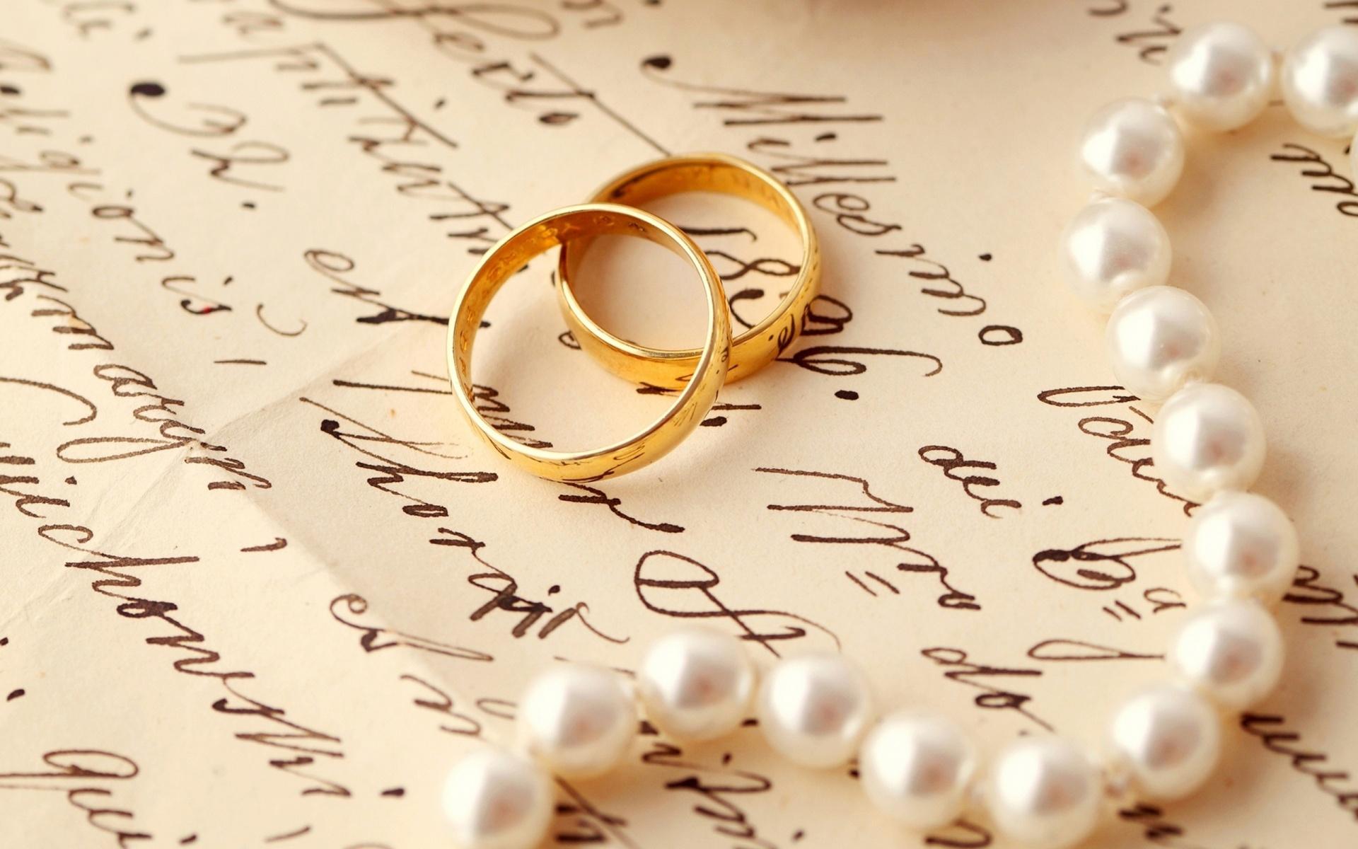 Dos anillos y collar sobre un texto manuscrito.