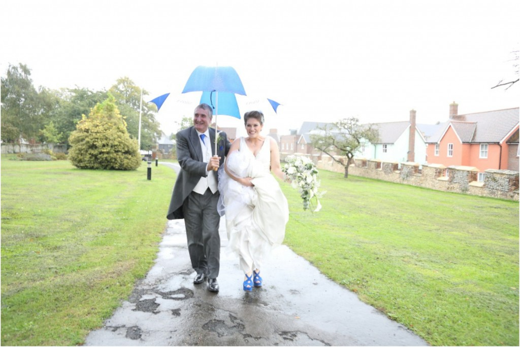 walking to the church in the rain at essex wedding