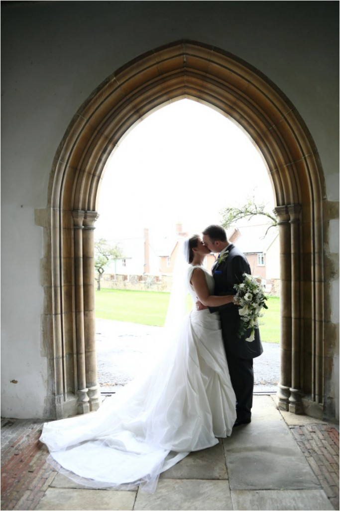 kiss in the archway of the church at essex wedding