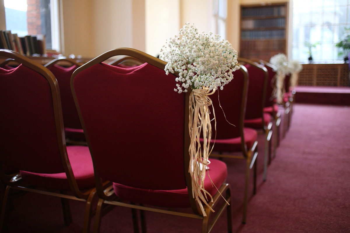 flowers on chairs at cambridge union society wedding