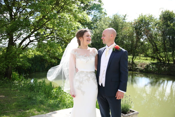 laughing bride by the lake at sunny barn wedding in saffron walden