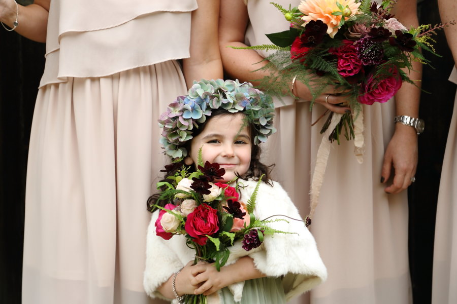 beautiful flower girl close up shot with bridesmails in background, quirky fun