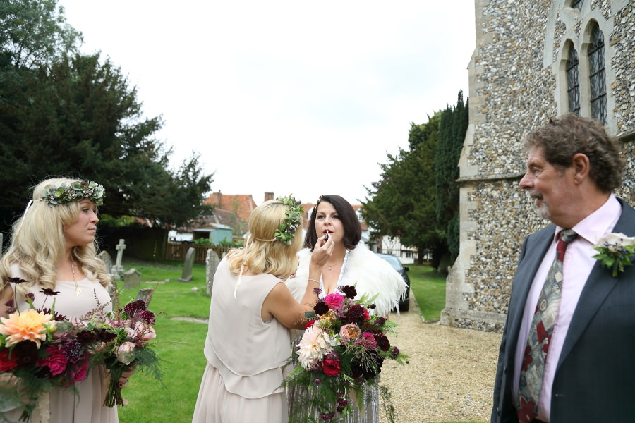 re-applying the lipstick on the bride before wedding at manuden church, essex
