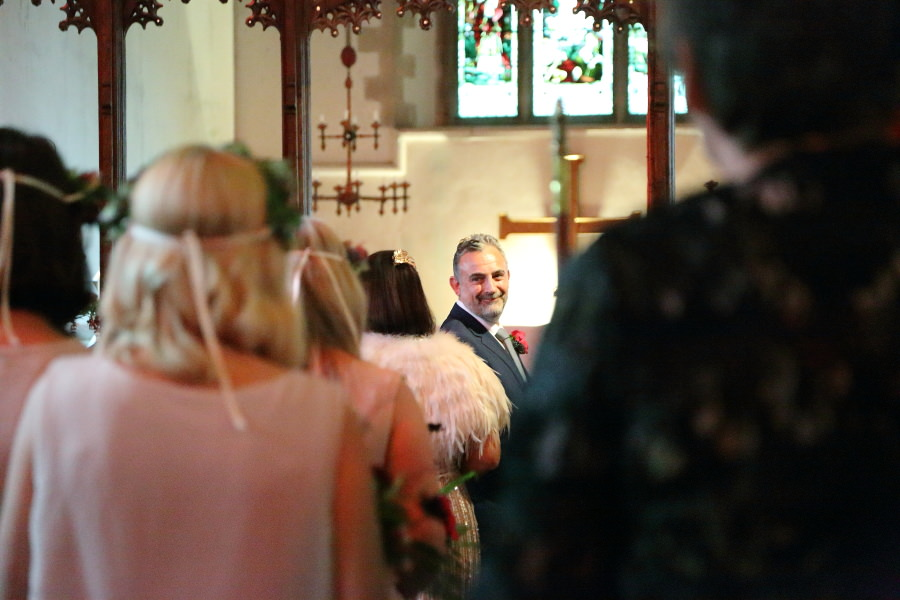 groom watching the bride walk along the isle at manuden church, essex