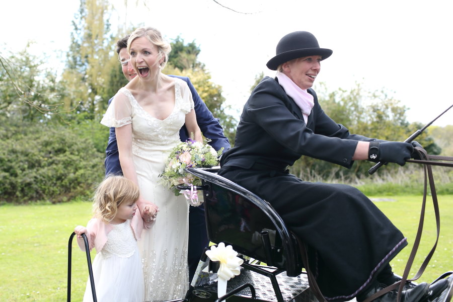 bride groom and flower girl leaving church on horse and carraige