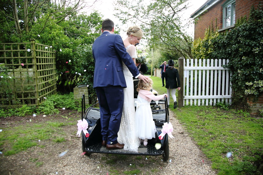 married couple leaving church wedding on horse and cart