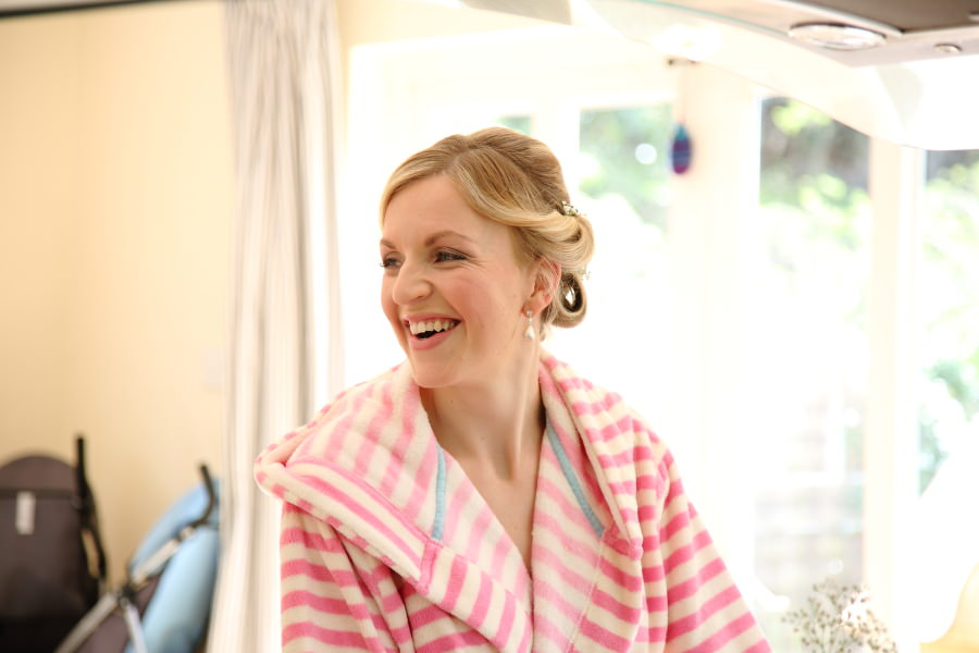 laughing bride as she gets ready at home for fun essex wedding