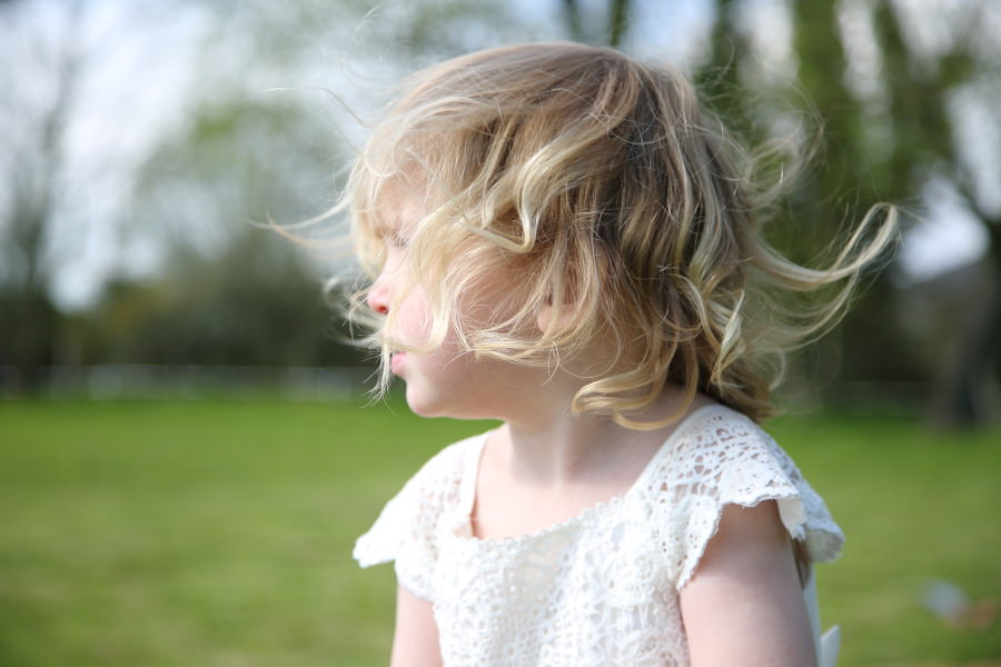 blonde child with hair blowing in the wind at hempstead tipi wedding
