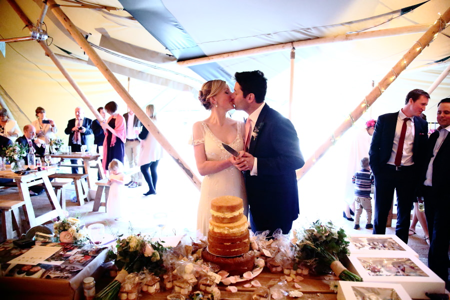 relaxed couple cutting the wedding cake at tipi wedding