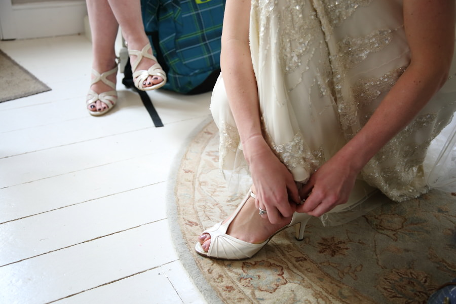 putting shoes on, the bride on her wedding day in essex, documentary wedding photography