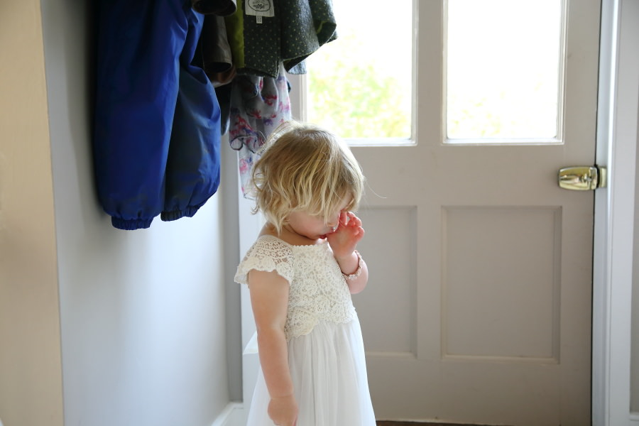 young flowergirl sucking her thumb before the wedding, hempstead wedding in essex, documentary wedding photography