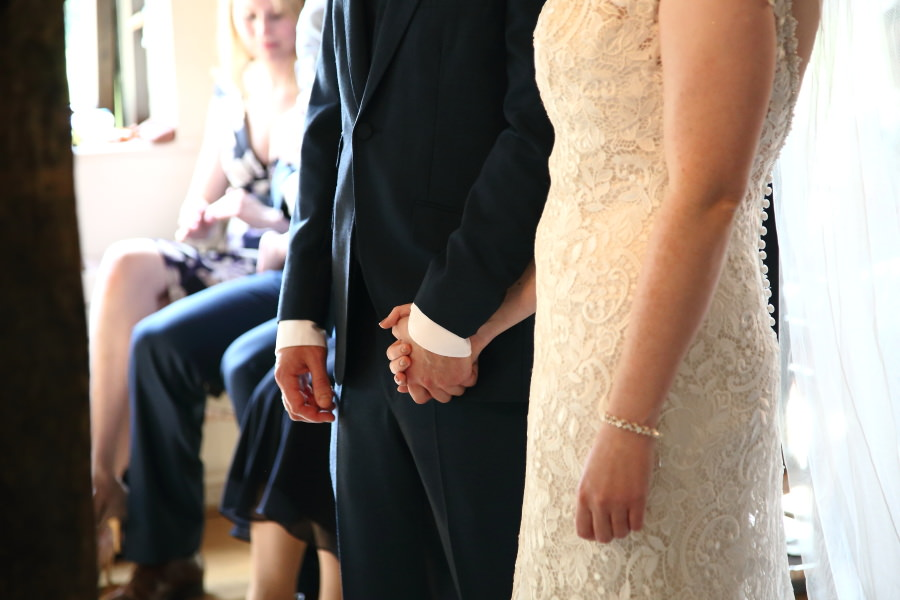 bride and groom hold hands during ceremony, newmarket wedding photography