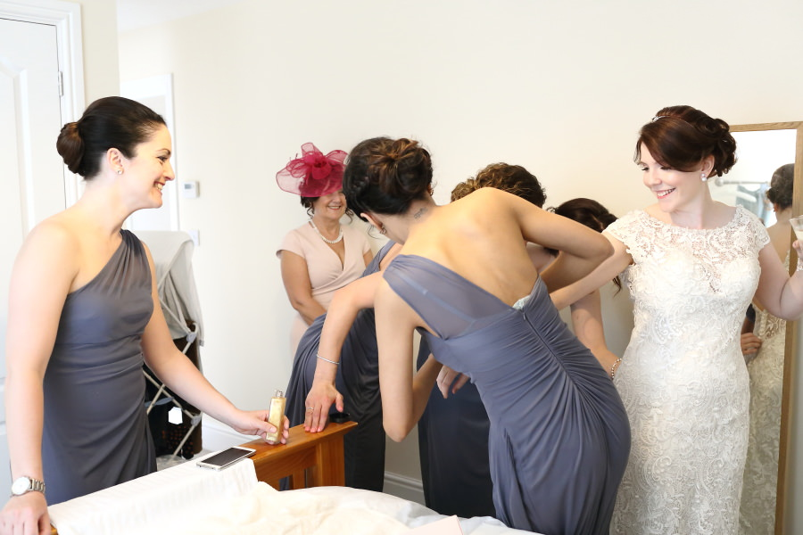 all bridesmaids helping bride get ready