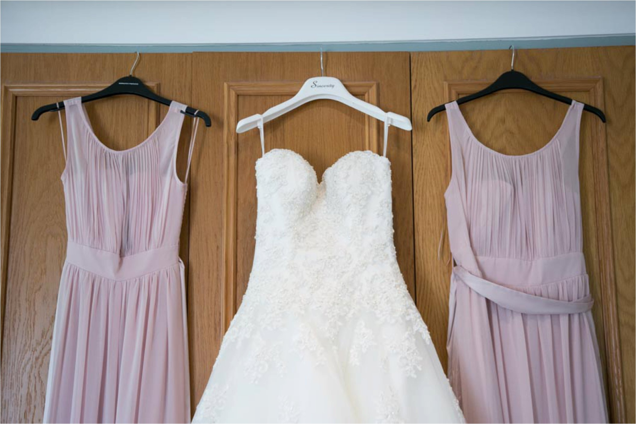 ducky pink bridesmaid dressed hanging up with wedding dress