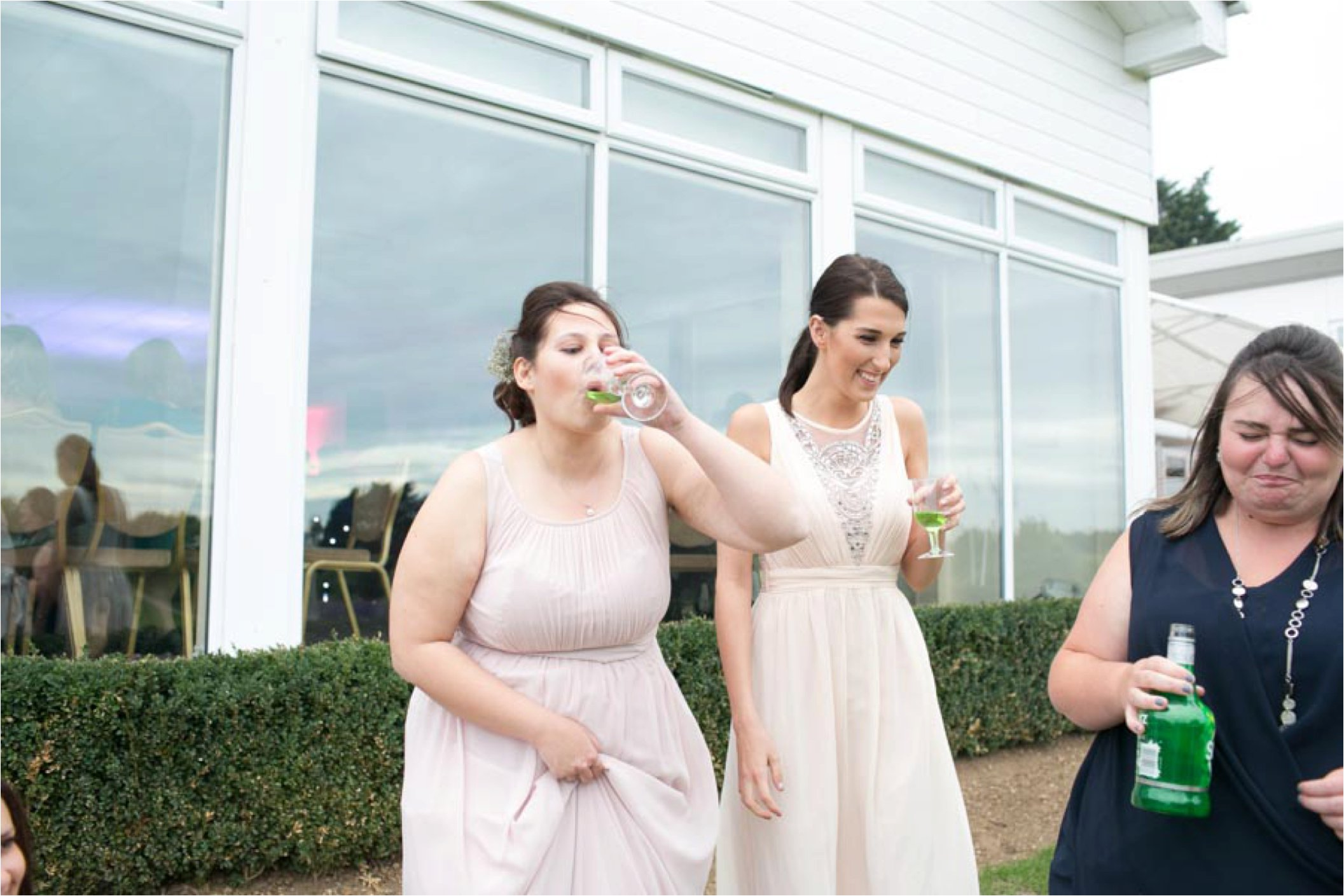 fun photo of bridesmaids sneeking shots at wedding, stoke by nayland golf club