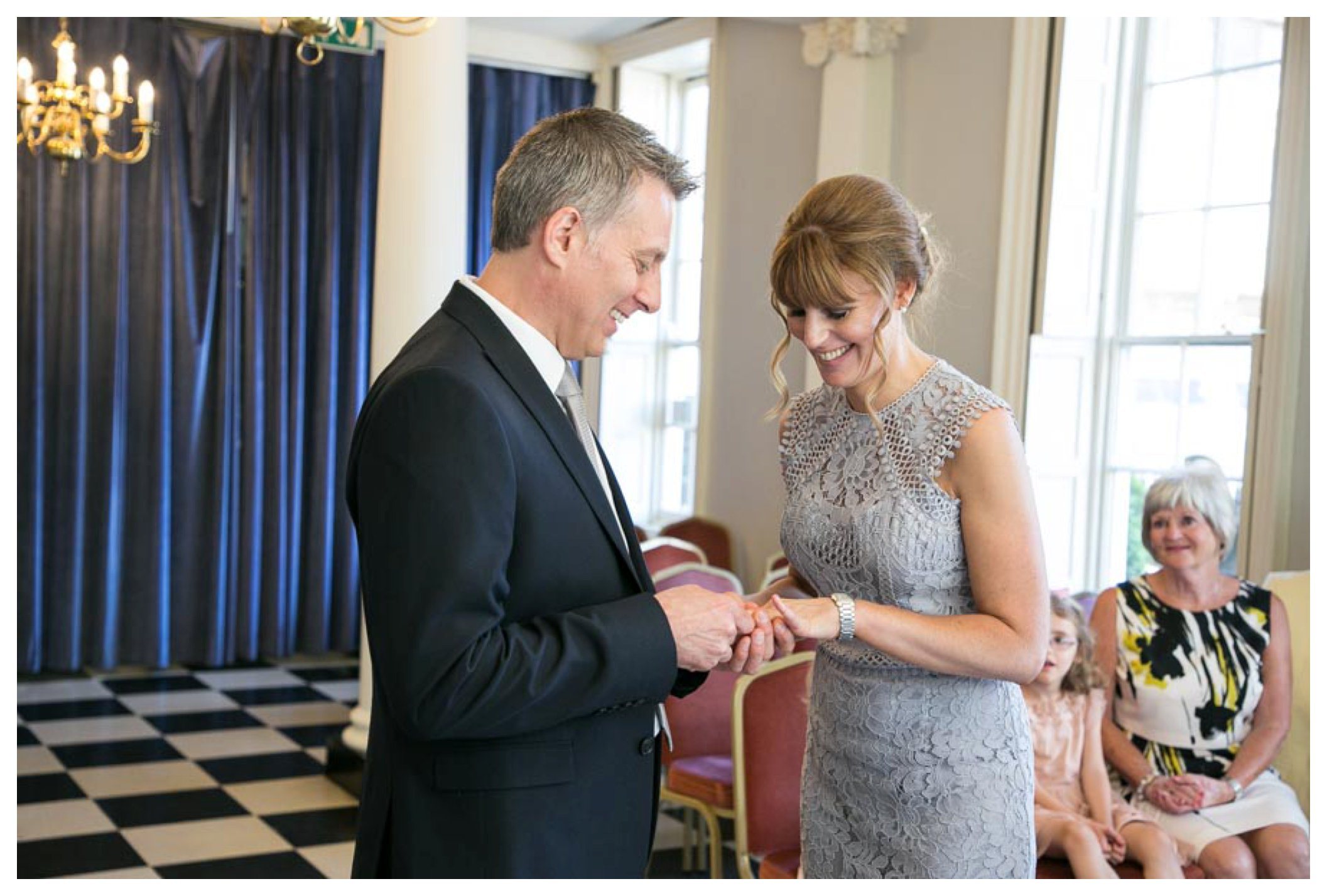 relaxed bride and groom putting ring on finger at registry office