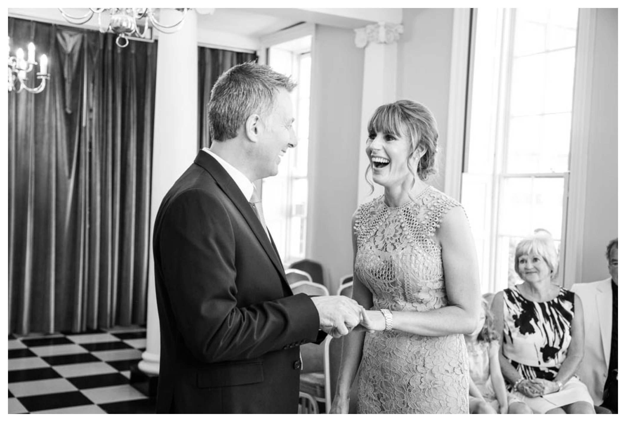 laughing bride in black and white image at regsiter office wedding bury st edmunds