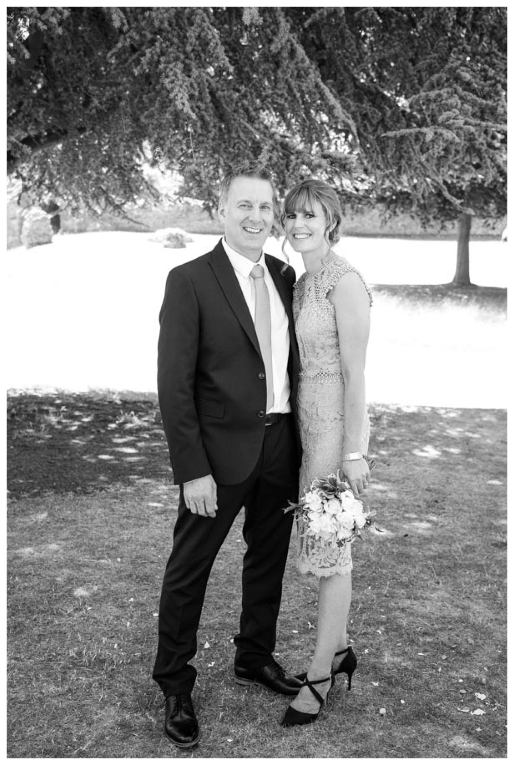black and white image just married couple loooking at camera smiling