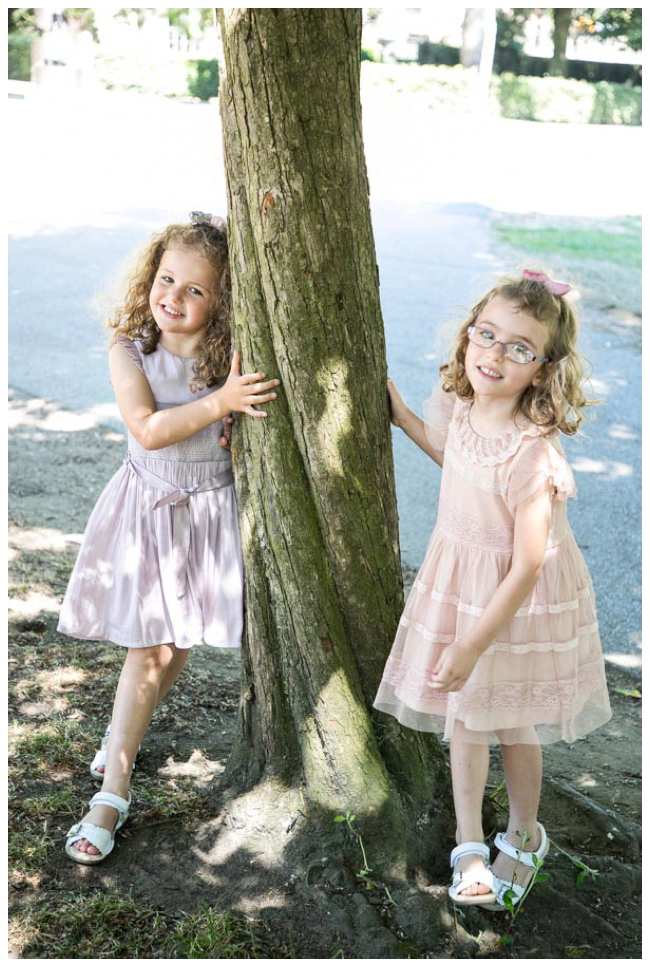twin girls on either side of a tree at wedding