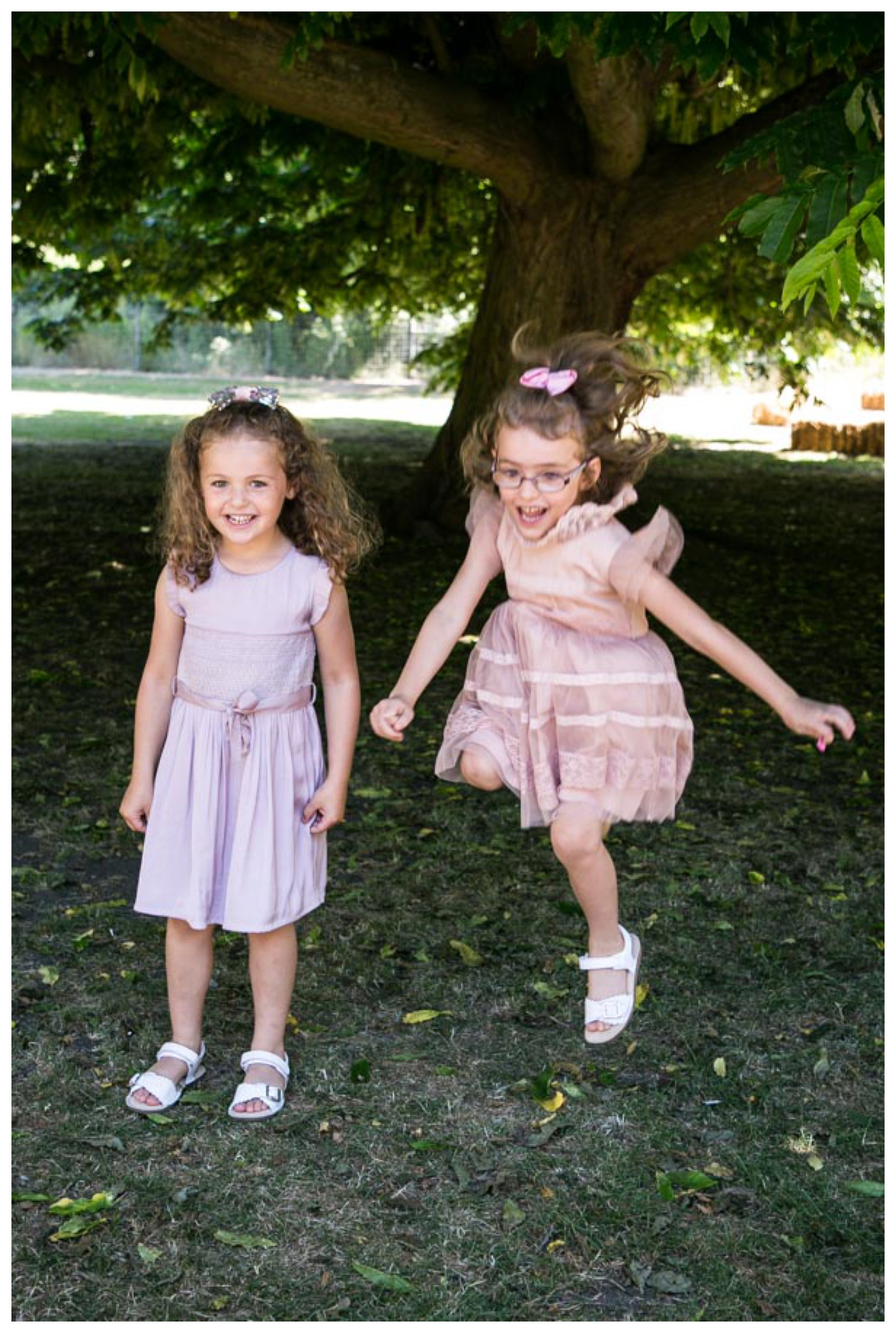 twin girls, one jumping, by large tree