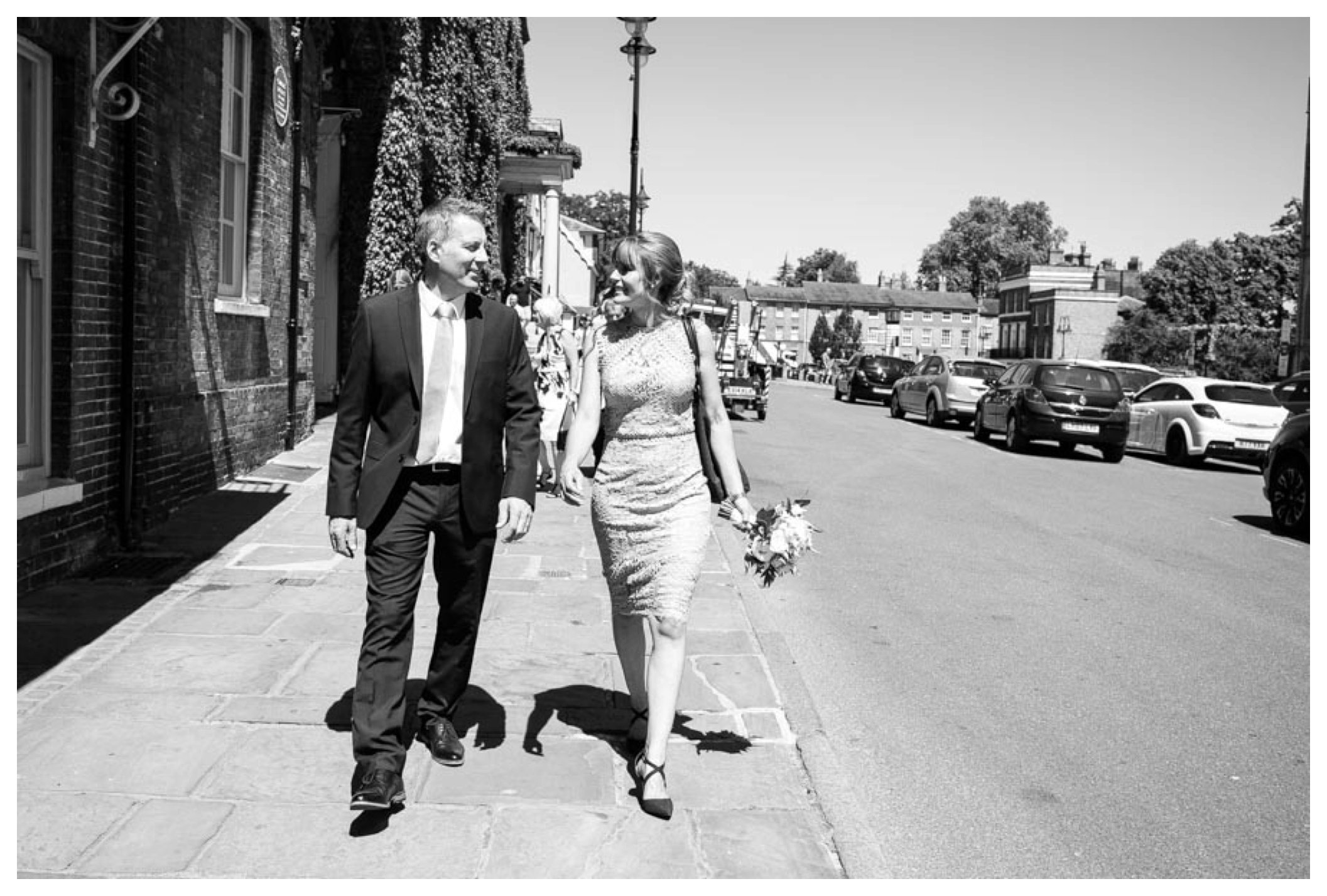 black and white, bride and groom smailing at each other as walk along in bury st edmunds