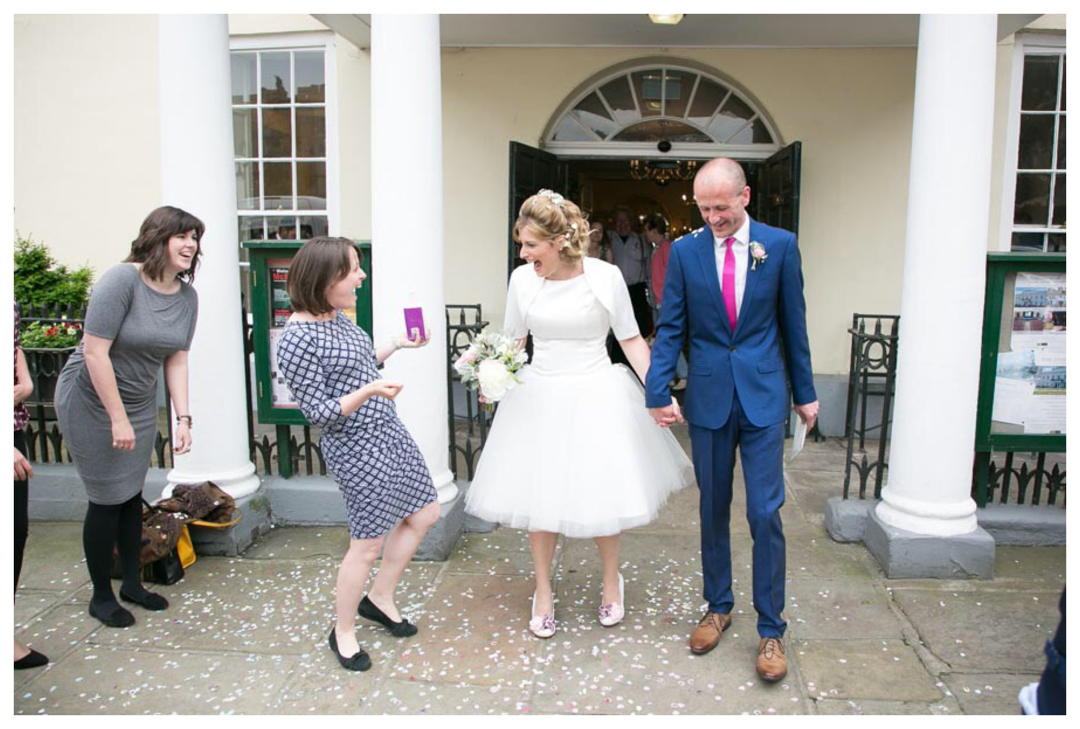 bride laughing at guest as she exits wedding at Athenaeum Bury St Edmunds