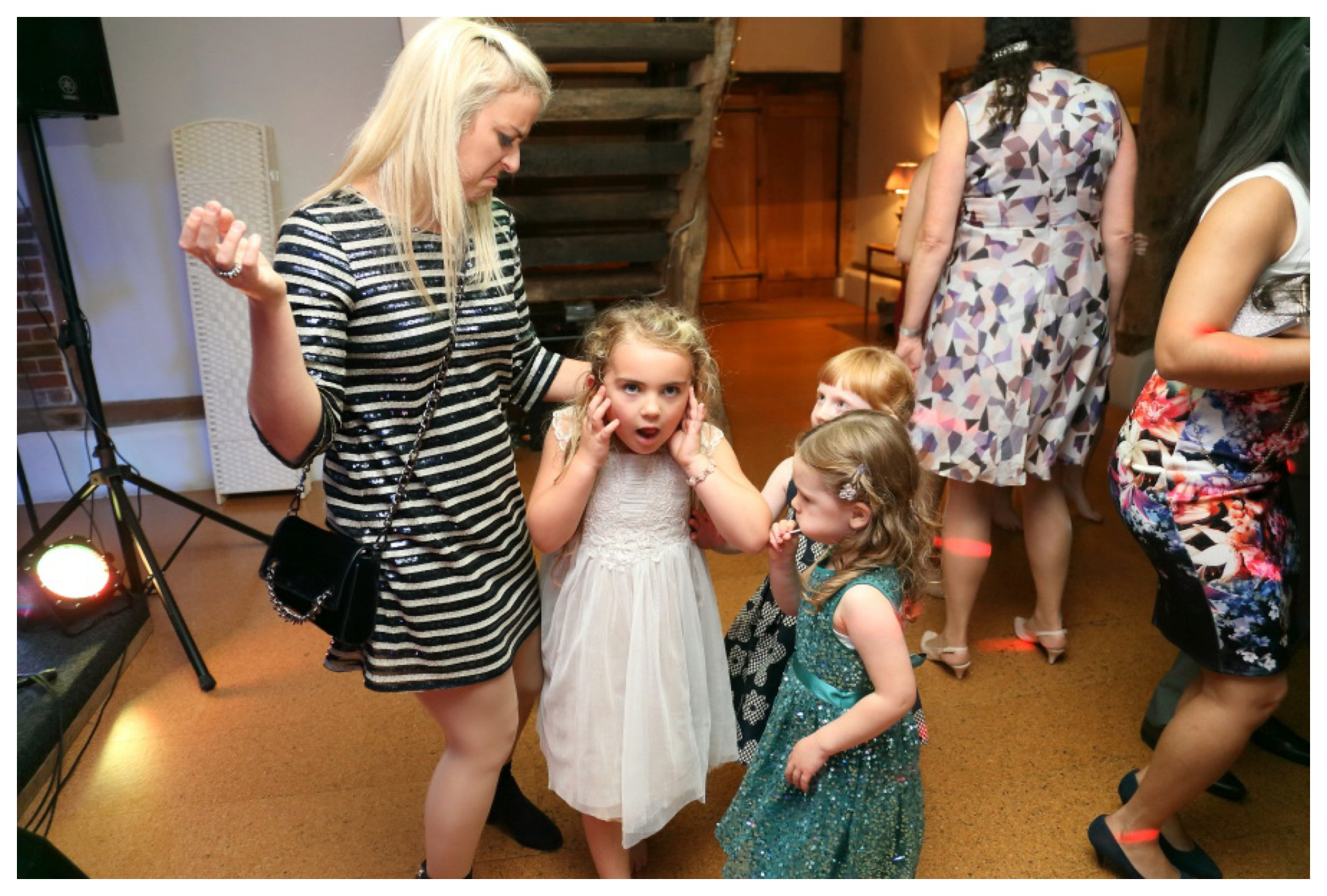 little girl with fingers in her ears at wedding reception in suffolk