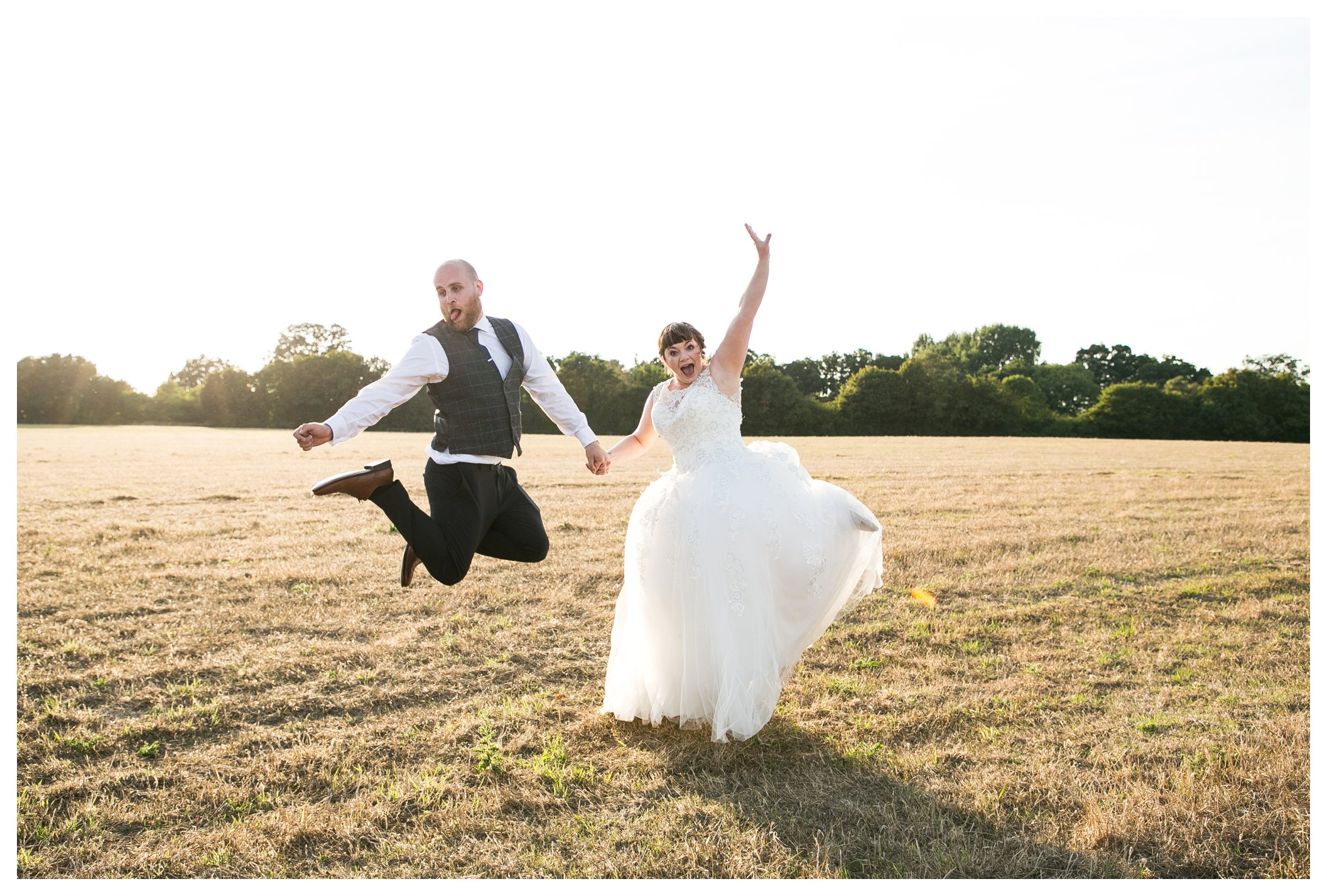 bride and groom jumping for joy in a suffolk field on their wedding day