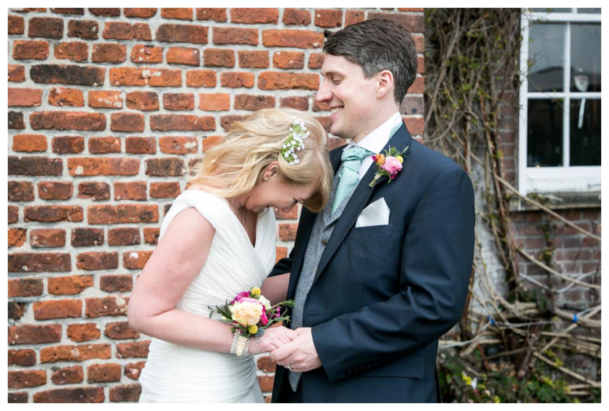 bride and groom standing by a brick wall at Anstey Hall in Cambridge