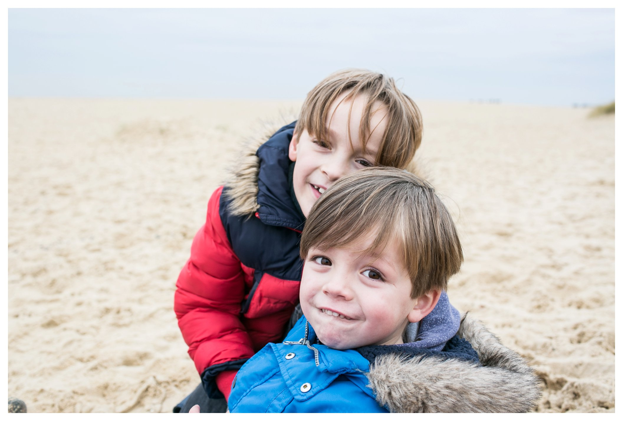 brothers portrait red and blue coats on southwold beach