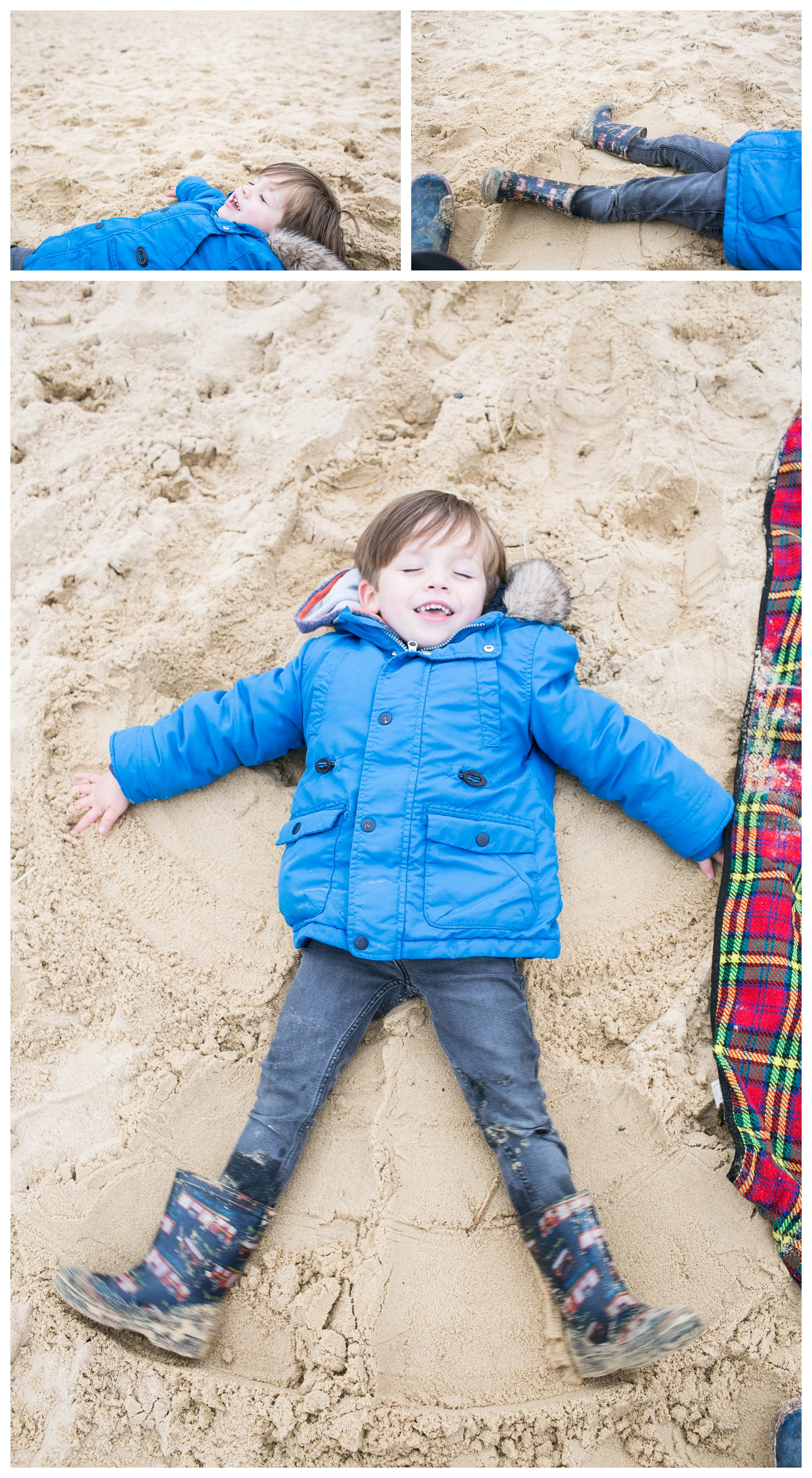 boy in blue coat making sand angels on southwold beach
