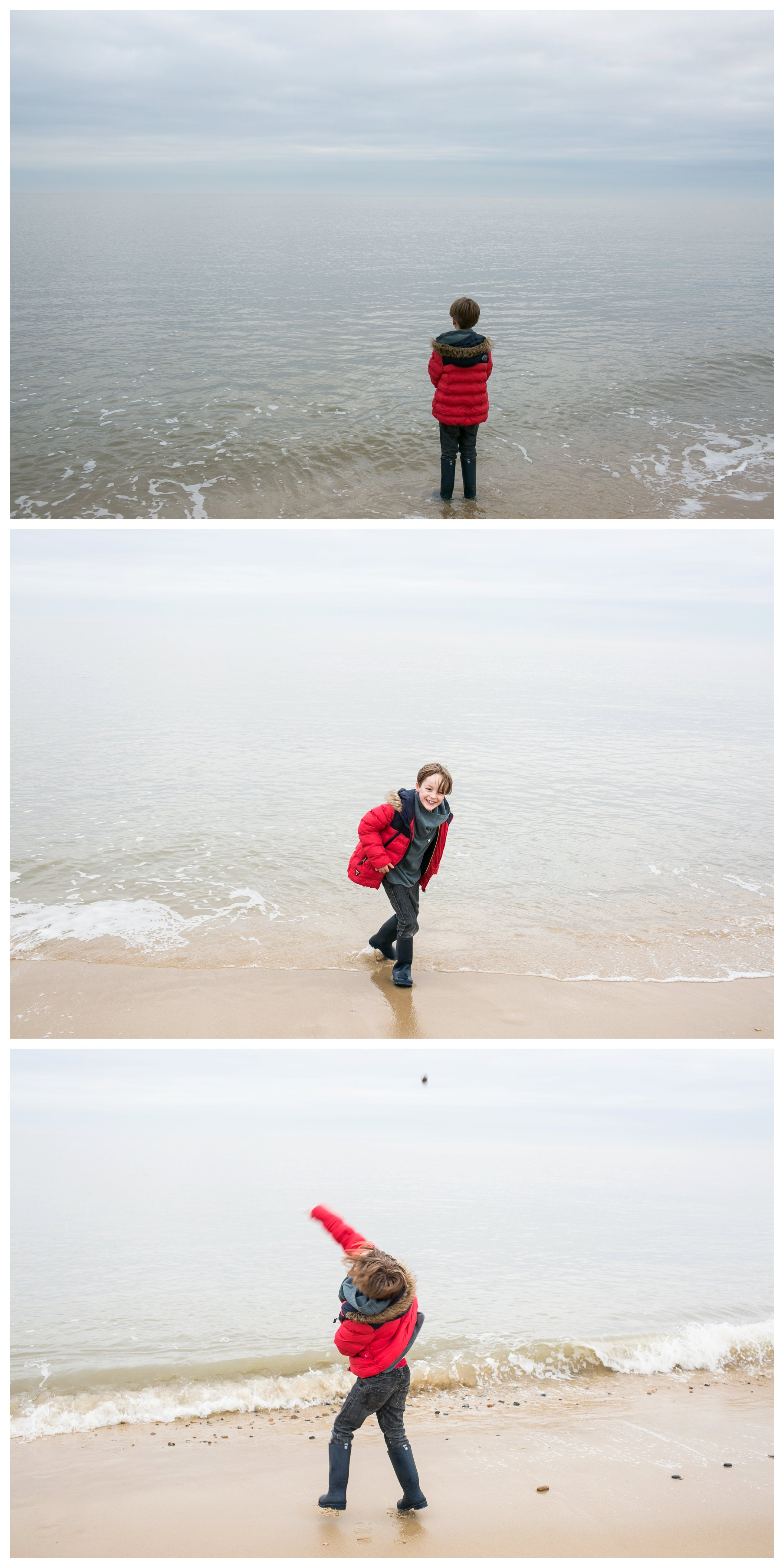 boy in red coat throwing stones into the sea