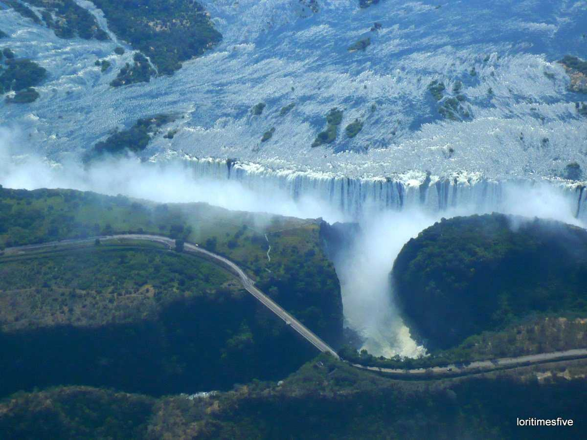 We asked our pilot if he wouldn't mind taking a turn around the falls so we could have another look, an aerial look. Here you can see the Zambezi bridge, on the left is Zimbabwe and on the right, Zambia ...