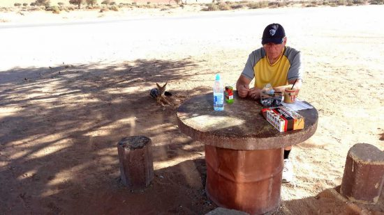 """""""Returning to our vehicle at the Deadvlei parking lot we decided it was snack time so out came the peanut butter and crackers where we sat at a cement table and stools. All of a sudden we noticed 2 black backed jackals approach us but not coming too close, just laying on the ground beside us waiting for whatever food we had to offer them."""""""