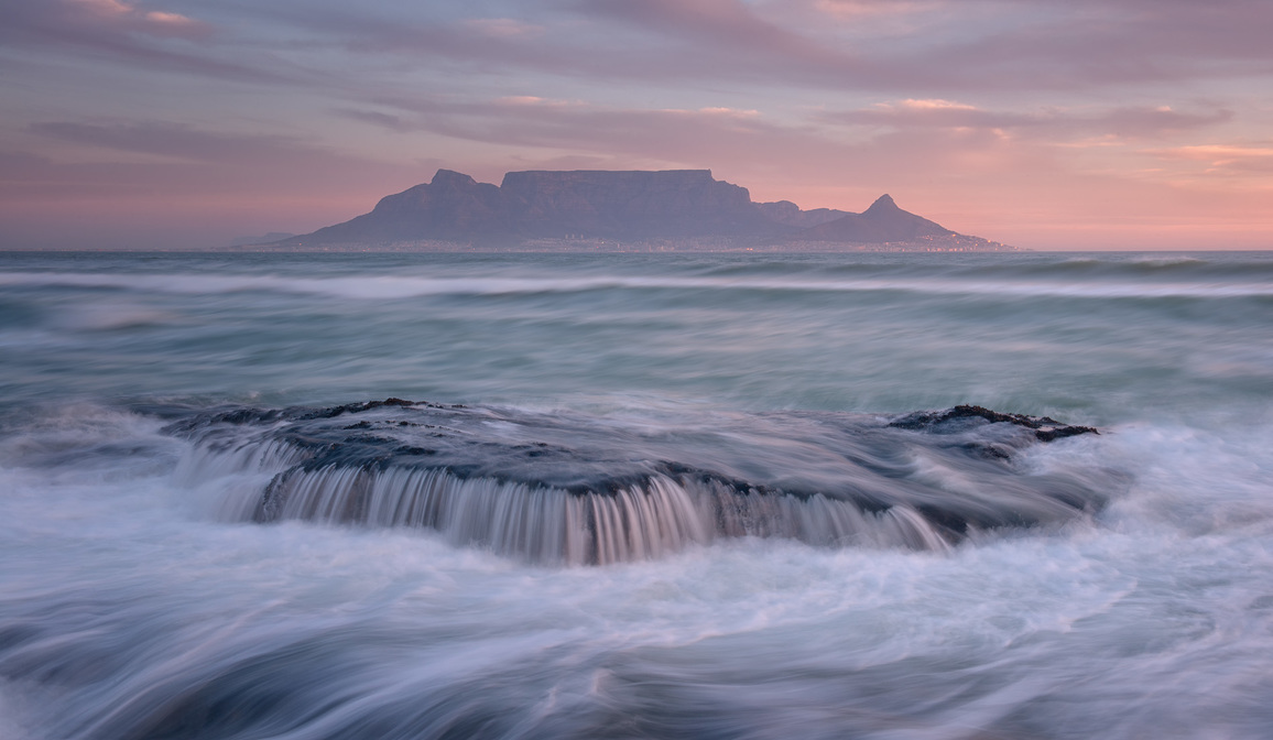 Long exposure of Table Mountain as seen from the rocks at the end of Blaauwberg beach.